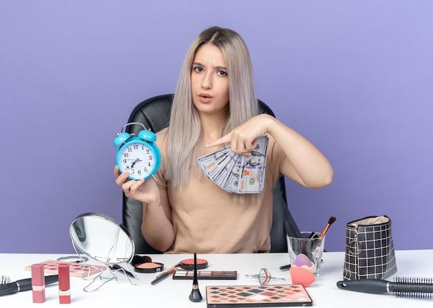 Niezadowolona młoda piękna dziewczyna siedzi przy stole z narzędziami do makijażu, trzymając w dłoni gotówkę i punkty przy budziku na białym tle na niebieskim tle