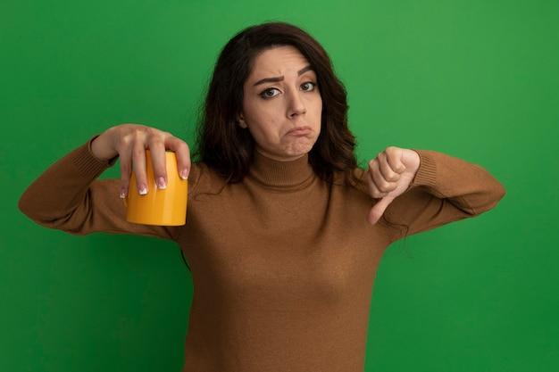 Niezadowolona młoda piękna dziewczyna trzyma filiżankę herbaty i pokazuje kciuk w dół na białym tle na zielonej ścianie