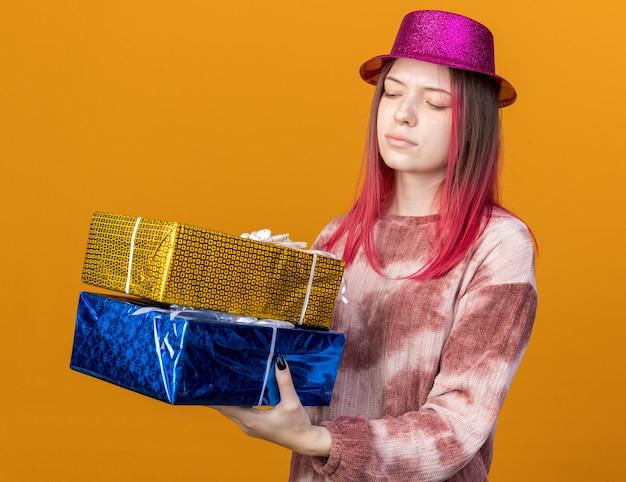 Niezadowolona młoda piękna dziewczyna w kapeluszu imprezowym, trzymająca i patrząca na pudełka z prezentami