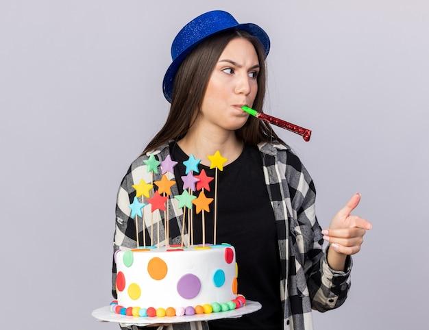 Niezadowolona młoda piękna dziewczyna w kapeluszu imprezowym trzymająca punkty ciasta dmuchająca gwizdek imprezowy na białej ścianie