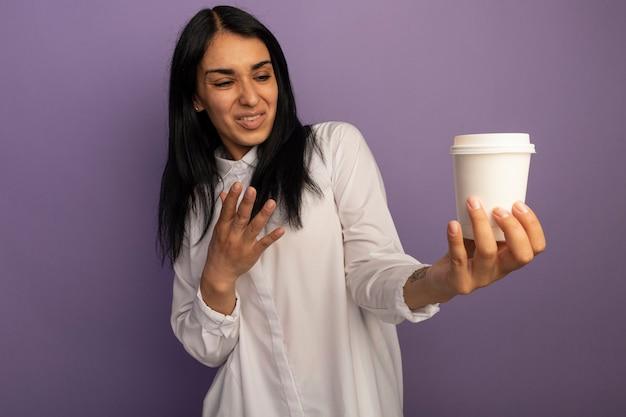 Niezadowolona młoda piękna kobieta ubrana w białą koszulkę trzyma i wskazuje ręką na filiżankę kawy