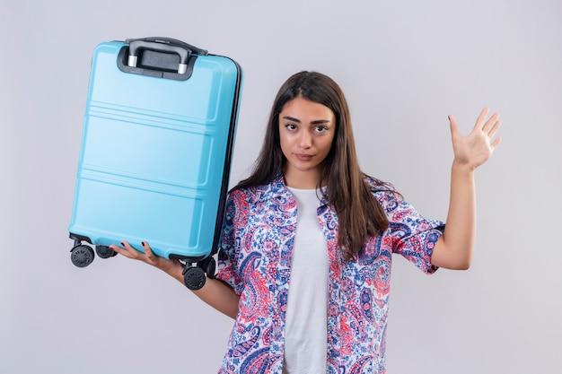 Niezadowolona młoda piękna podróżniczka trzyma walizkę z otwartą ręką robi gest stopu na białej ścianie