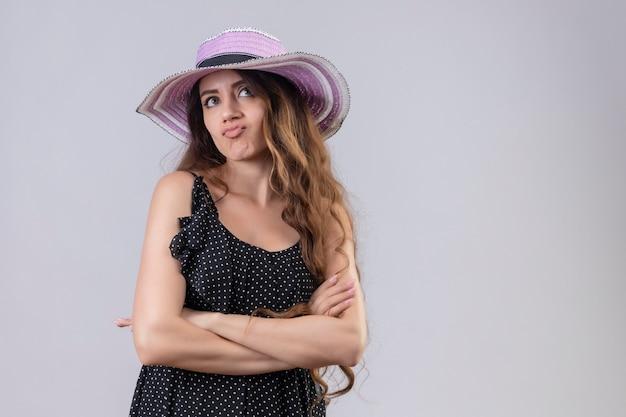 Niezadowolona młoda piękna podróżniczka w letnim kapeluszu stojącym z rękami skrzyżowanymi stojąc