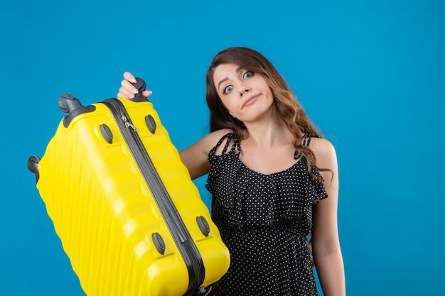 Niezadowolona młoda piękna podróżniczka w sukience w groszki trzyma walizkę z zmieszanym wyrazem twarzy stojącej nad niebieską przestrzenią