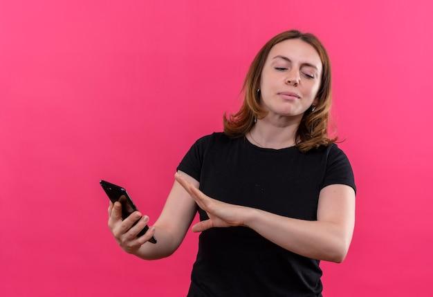 Niezadowolona młoda przypadkowa kobieta trzyma telefon komórkowy i gestykuluje nie na odosobnionej różowej ścianie
