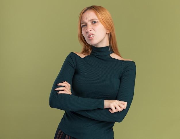 Niezadowolona młoda rudowłosa ruda dziewczyna z piegami stoi ze skrzyżowanymi rękami patrząc na kamery na oliwkowej zieleni