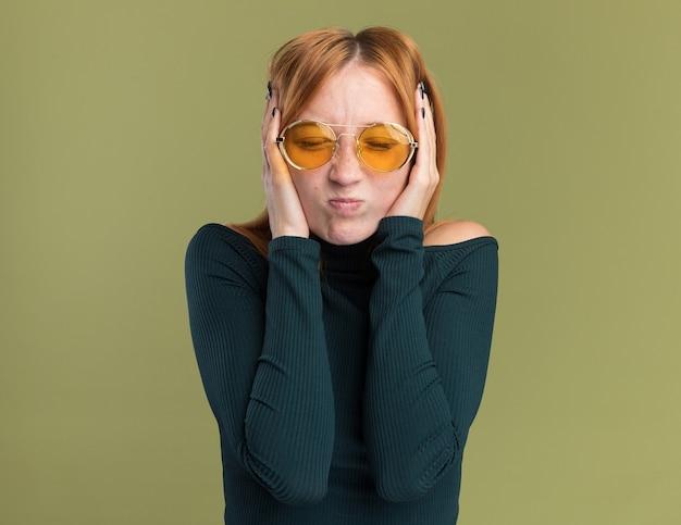 Niezadowolona młoda rudowłosa ruda dziewczyna z piegami w okularach przeciwsłonecznych stoi z zamkniętymi oczami, trzymając głowę na oliwkowej zieleni