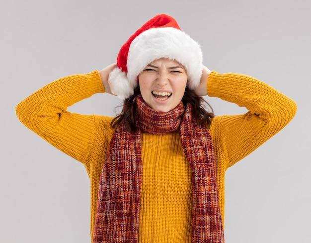 Niezadowolona młoda słowiańska dziewczyna z czapką mikołaja iz szalikiem na szyi trzyma głowę na białym tle na białym tle z miejsca na kopię