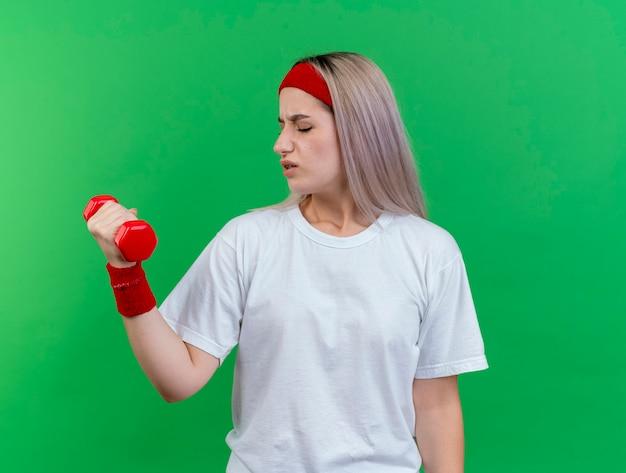 Niezadowolona młoda sportowa dziewczyna rasy kaukaskiej z szelkami w opasce na głowie i nadgarstkach trzyma hantle