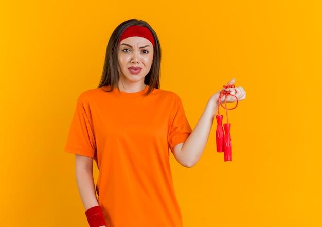 Niezadowolona młoda sportowa kobieta ubrana w opaskę i opaski na rękę trzyma skakankę odizolowaną na pomarańczowej ścianie z miejscem na kopię