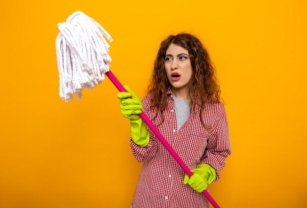 Niezadowolona młoda sprzątaczka w rękawiczkach, trzymająca i patrząca na mopa