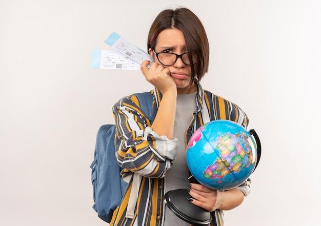 Niezadowolona młoda studentka w okularach i plecak trzyma bilety lotnicze i kula ziemska na białym tle na białym tle z miejsca na kopię