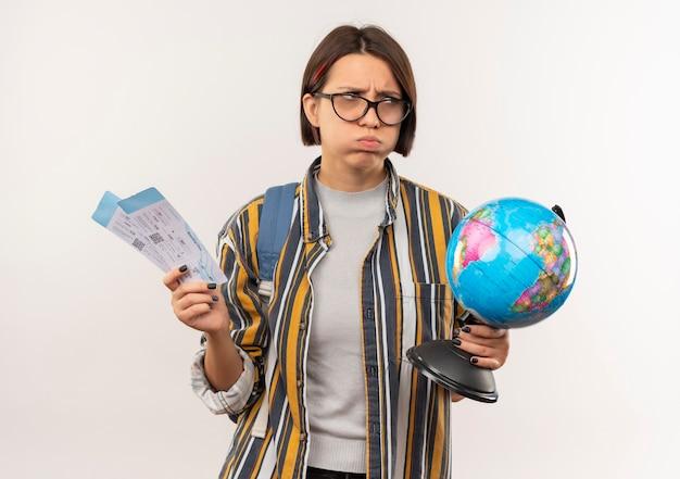 Niezadowolona młoda studentka w okularach i plecak trzyma bilety lotnicze i kula ziemska patrząc z boku na białym tle