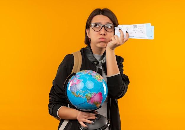 Niezadowolona młoda studentka w okularach i plecaku trzymająca bilety lotnicze i kula ziemska patrząc z boku patrząc z boku na białym tle na pomarańczowym tle z miejscem na kopię