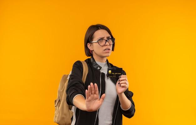 Niezadowolona młoda studentka w okularach i torbie z tyłu trzyma kartę kredytową gestykuluje stop na białym tle na pomarańczowym tle z miejsca na kopię