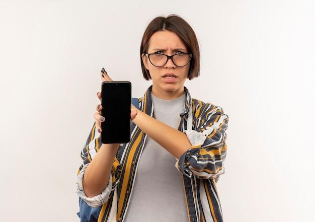 Niezadowolona młoda studentka w okularach i tylnej torbie pokazująca telefon komórkowy nie wykonująca żadnego gestu z boku na białym tle na białym tle z miejsca na kopię
