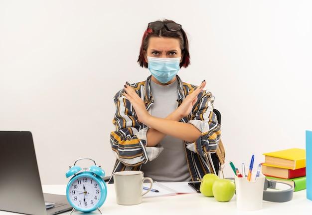 Niezadowolona młoda studentka w okularach na głowie i masce siedzi przy biurku z narzędziami uniwersyteckimi, gestykulacji nie na białym tle