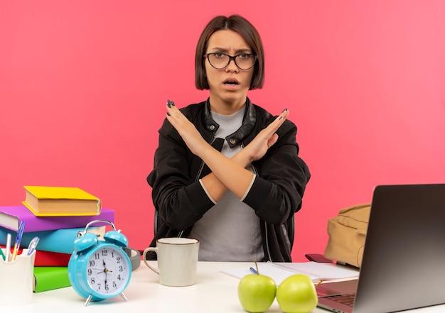 Niezadowolona młoda studentka w okularach siedzi przy biurku z narzędziami uniwersyteckimi, odrabiając pracę domową, gestykulacji nie na białym tle na różowym tle