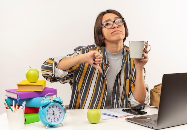 Niezadowolona młoda studentka w okularach siedzi przy biurku z narzędziami uniwersytetu, trzymając filiżankę kawy i pokazując kciuk w dół na białym tle