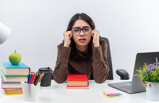 Niezadowolona młoda szkolna kobieta w okularach siedzi przy stole z szkolnymi narzędziami trzymając się za ręce na policzkach