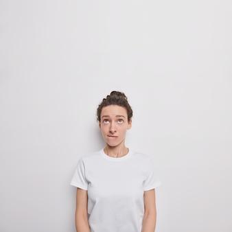 Niezadowolona młoda tysiącletnia kobieta przygryza usta skupione nad sobą, słucha czegoś z uważnym spojrzeniem w górę pozuje na białej ścianie