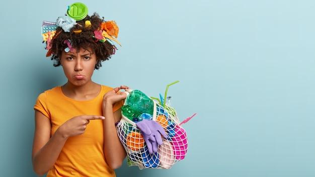 Niezadowolona modelka o czarnej skórze, zbiera śmieci, z niezadowoleniem wskazuje na plastikowe odpady, pracuje jako wolontariusz, chroni środowisko, stoi nad niebieską ścianą z wolnym miejscem na tekst