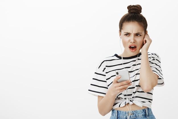Niezadowolona narzekająca dziewczyna wygląda na rozczarowaną, słucha okropnej muzyki lub podcastu w słuchawkach, trzymając telefon komórkowy