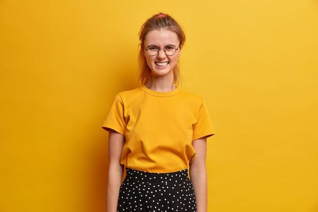 Niezadowolona nastolatka marszczy brwi twarz zaciska zęby ze złości stara się powstrzymać emocje w sobie irytację z jakiegoś powodu