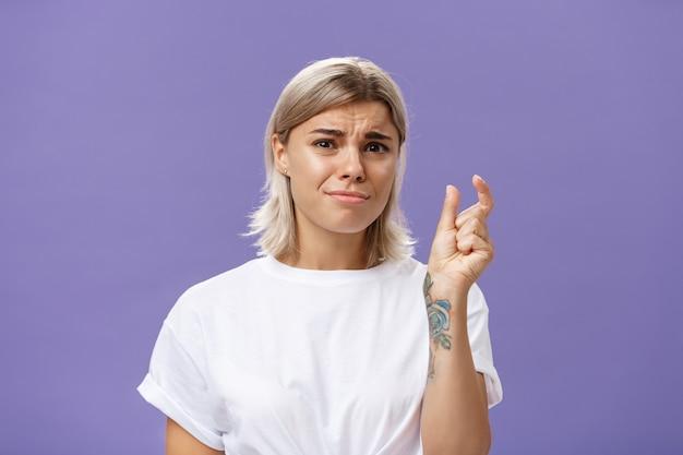 Niezadowolona, niezadowolona dziewczyna marszczy brwi i wydyma usta, kształtując malutki przedmiot