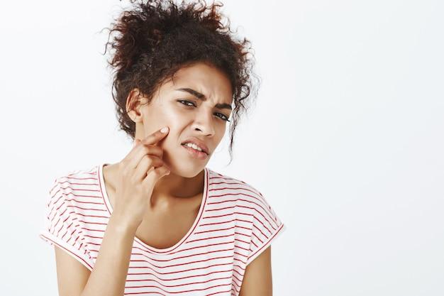 Niezadowolona niezadowolona kobieta z fryzurą afro pozowanie w studio