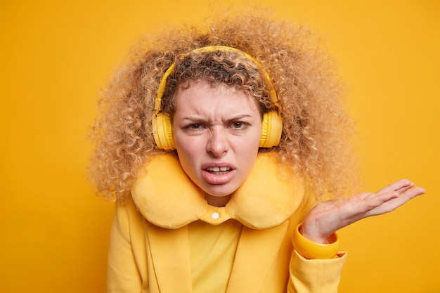 Niezadowolona, oburzona kobieta z kręconymi włosami unosi dłonie z uśmieszkami na twarzy nosi słuchawki stereo nie lubi czegoś ubranego w żółte ubrania jednym tonem ze ścianą wyraża negatywne emocje