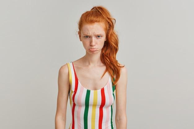 Niezadowolona pani, smutna kobieta z rudym kucykiem i piegami, ubrana w kolorowy kostium kąpielowy w paski