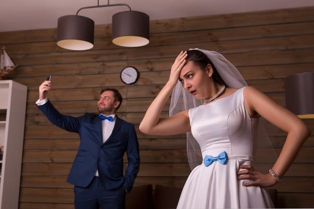 Niezadowolona panna młoda i pan młody robi selfie na drewnianym pokoju