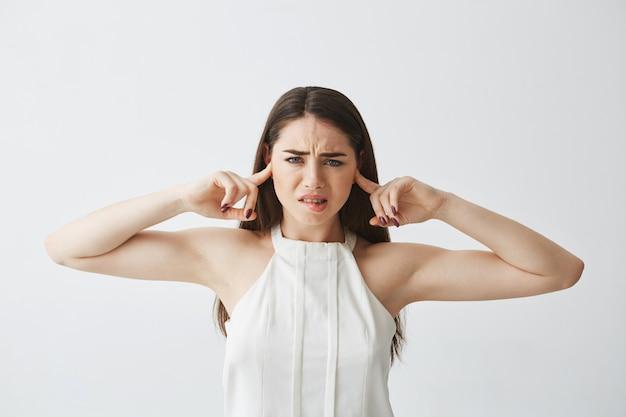Niezadowolona piękna brunetka dziewczyna zamykając uszy palcami od gryzącej wargi.