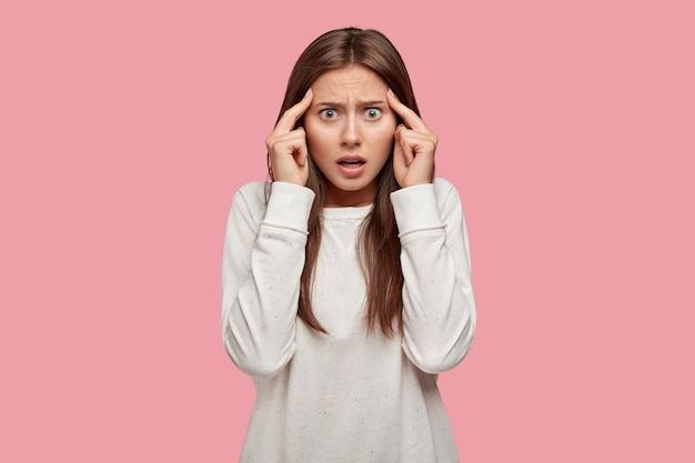 Niezadowolona piękna brunetka pozująca na różowej ścianie