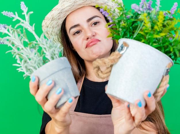 Niezadowolona piękna dziewczyna ogrodnik w mundurze na sobie kapelusz ogrodniczy, trzymając kwiat w doniczce na białym tle