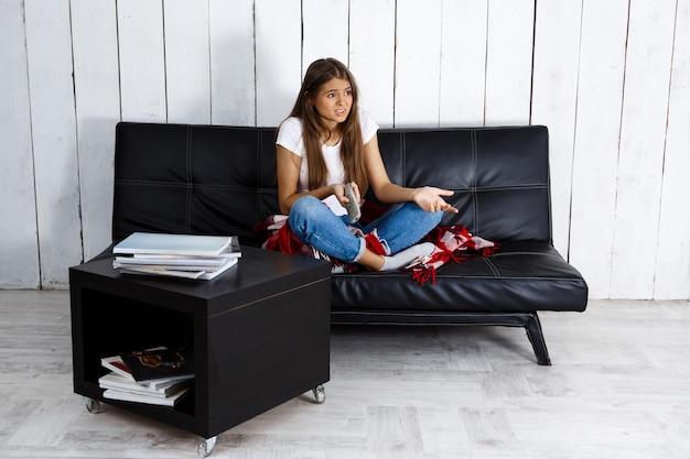 Niezadowolona piękna kobieta ogląda telewizję, siedzi na kanapie w domu.