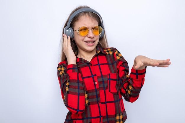 Niezadowolona piękna mała dziewczynka ubrana w czerwoną koszulę i okulary ze słuchawkami