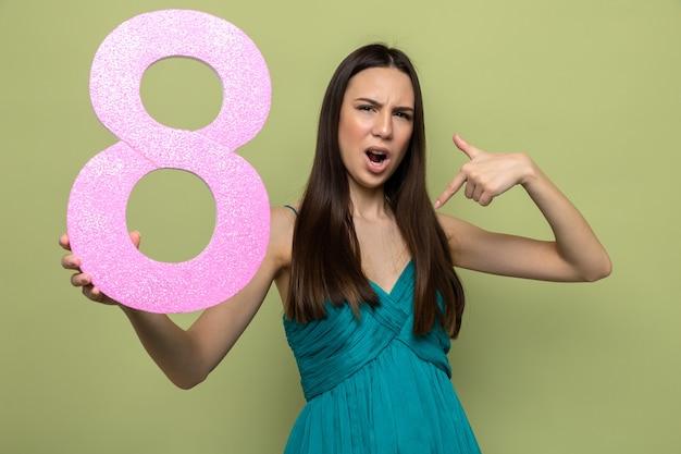 Niezadowolona piękna młoda dziewczyna na szczęśliwy dzień kobiet trzyma i wskazuje na numer osiem