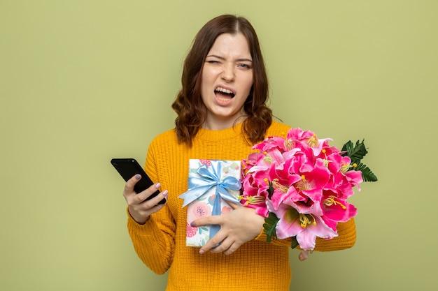 Niezadowolona piękna młoda dziewczyna trzyma prezenty z telefonem