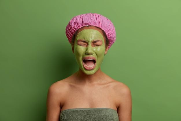 Niezadowolona płacząca kobieta czuje się zmęczona zabiegami kosmetycznymi w salonie spa, ma otwarte usta, nosi zieloną maskę dla idealnej skóry, nosi czepek i ręcznik dookoła ciała, stoi przy ścianie.