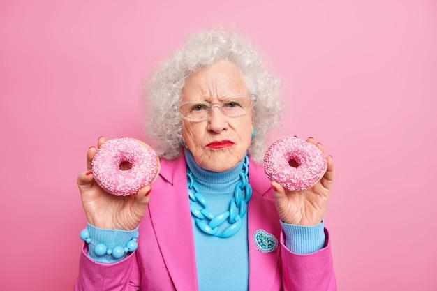 Niezadowolona, pomarszczona starsza kobieta trzyma dwa pyszne pączki, je niezdrowe jedzenie, nosi stylowy strój