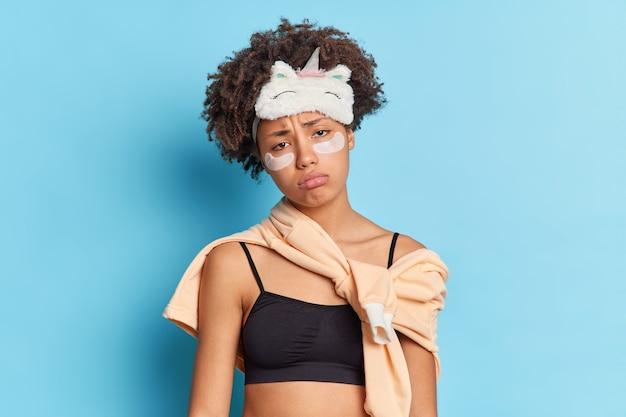 Niezadowolona ponura etniczna kobieta ze smutkiem patrzy z przodu ma wyczerpany wyraz twarzy chce mieć drzemkę zmęczoną po pracowitym dniu ubrana w bieliznę nocną