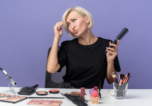 Niezadowolona przechylająca się głowa młoda piękna dziewczyna siedzi przy stole z narzędziami do makijażu, trzymając grzebień na białym tle na niebieskim tle