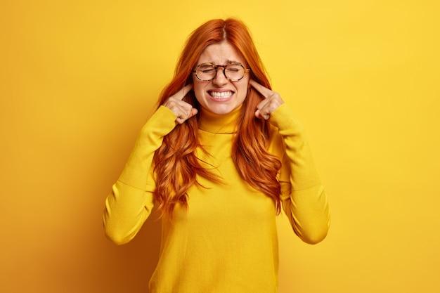 Niezadowolona ruda kobieta zaciska zęby i zatyka uszy, zirytowana głośnym dźwiękiem lub hałasem, nosi zwykły sweter.