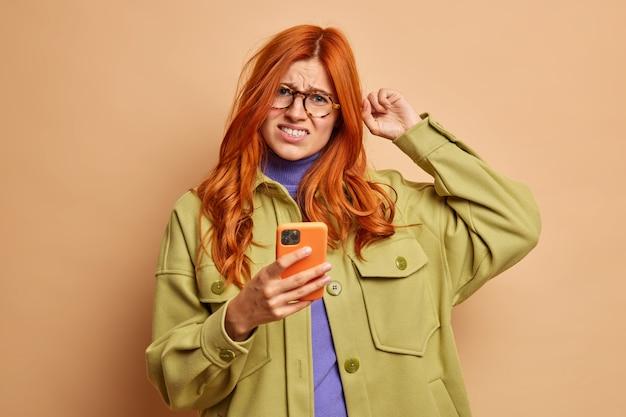 Niezadowolona rudowłosa kobieta drapie się po głowie marszcząc brwi z niezadowolenia, próbuje rozwiązać problem ze smartfonem nie wie, jak korzystać z nowej aplikacji ubrana w modne ciuchy.