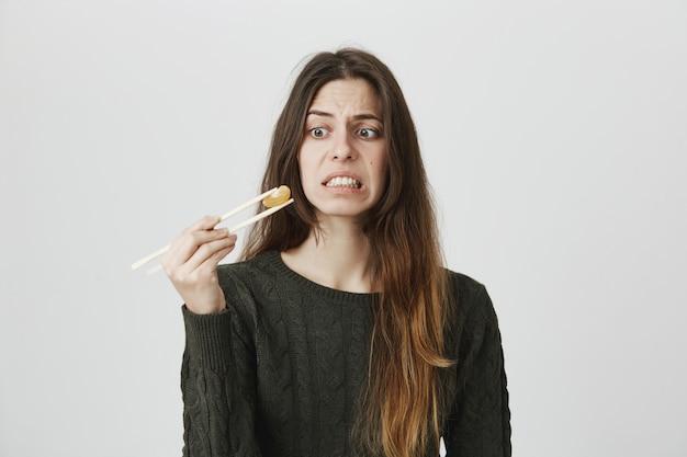 Niezadowolona, skrzywiona kobieta wpatrująca się w mandarynkę na pałeczkach