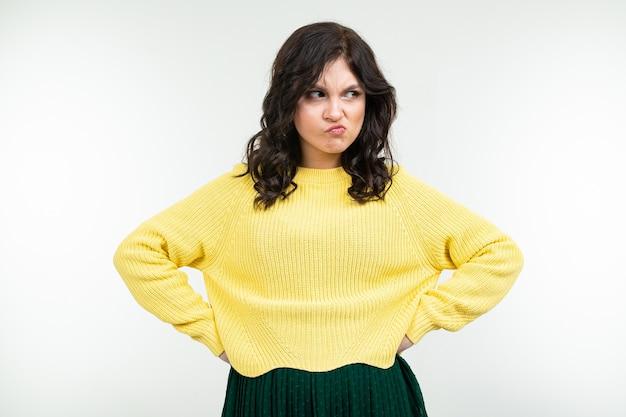Niezadowolona smutna brunetka dziewczyna w żółtym swetrze i zielonych spódnicach na białym tle
