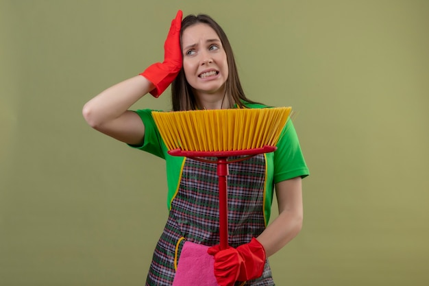 Niezadowolona sprzątaczka młoda dziewczyna ubrana w mundur w czerwonych rękawiczkach trzymająca mop położyła dłoń na głowie na odosobnionej zielonej ścianie
