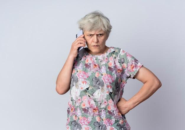 Niezadowolona starsza kobieta rozmawia przez telefon na białym tle na białej ścianie
